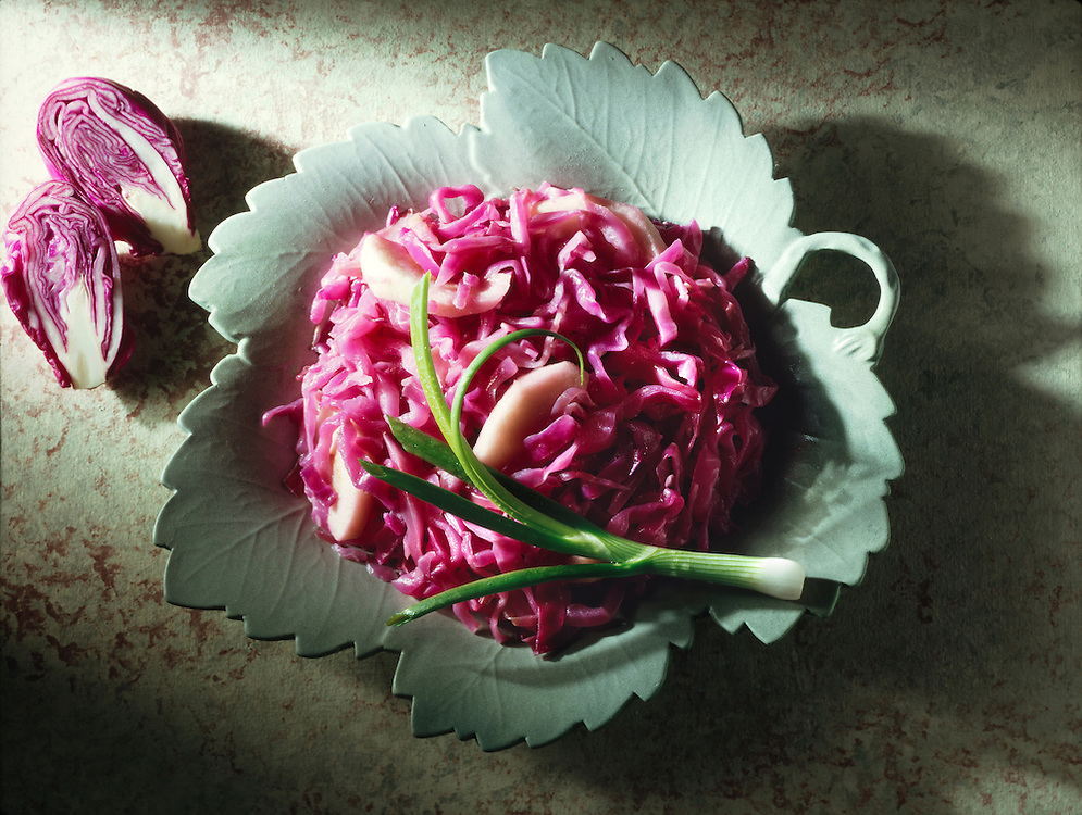Top shot of shredded red cabbage and apple salad on a grey leaf plate