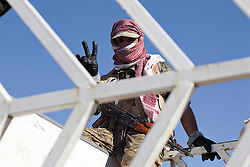 © Licensed to London News Pictures. 11/12/2014. Sinjar Mountains, Iraq. A Yazidi fighter makes a V for vistory sign from inside a truck on the top of Mount Sinjar.<br /> <br /> Although a well publicised exodus of Yazidi refugees took place from Mount Sinjar in August 2014 many still remain on top of the 75 km long ridge-line, with estimates varying from 2000-8000 people, after a corridor kept open by Syrian-Kurdish YPG fighters collapsed during an Islamic State offensive. The mountain is now surrounded on all sides with winter closing in, the only chance of escape or supply being by Iraqi Air Force helicopters. Photo credit: Matt Cetti-Roberts/LNP