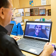 Dr. Rajan Kapoor, M.D. speaks on the Doxy.Me telemedicine web program to a patient who has questions about the Coronavirus (Covid-19) threat at Universal Medical Care on Tuesday, March 31, 2020 in Orlando, Florida. Universal Medical Care's patient load has been cut by fifty percent and they are currently referring patients with symptoms to local testing sites such as Centra Care or the site at the Orange County Convention Center. (Alex Menendez via AP)