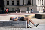 Young man lies back relaxing in the sunshine in the city centre in what was a positive atmosphere on the long awaited freedom day when all remaining coronavirus restrictions are lifted in the UK on 19th July 2021 in Birmingham, United Kingdom. While many people are wearing face masks, they are no longer mandatory, while government advice suggests that it is advised to wear a face covering in busy public places inside and on transport.
