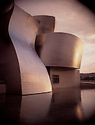 An exterior shot of the famous Guggenheim Museum reflecting in the water in Bilbao, Spain