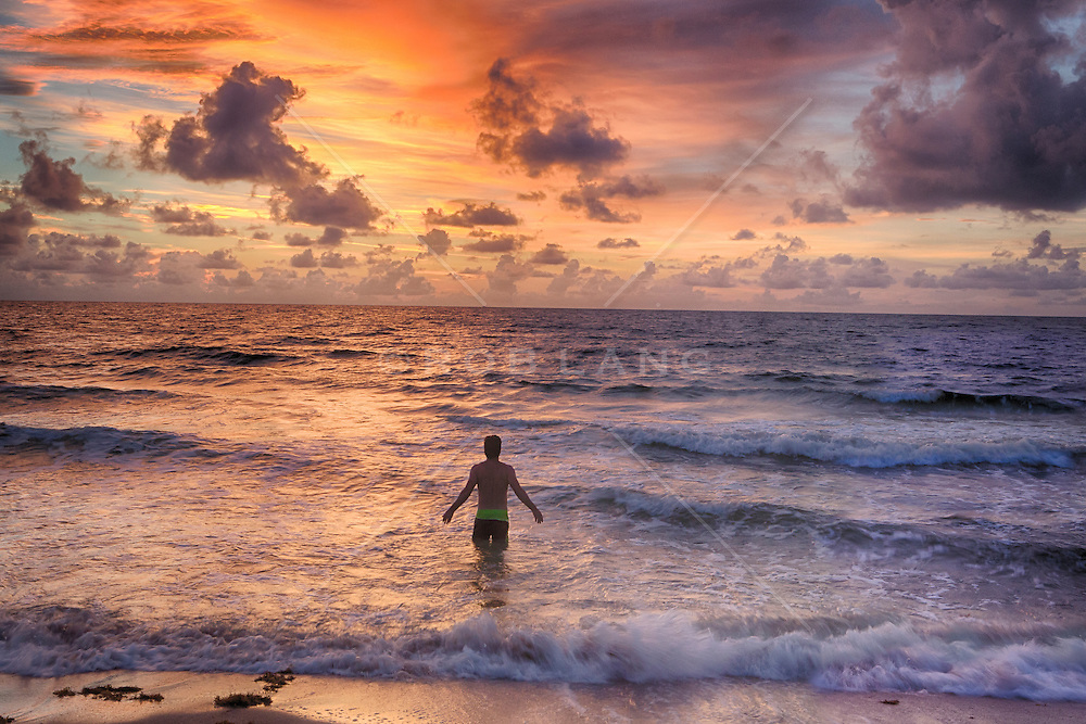 man standing in the ocean at sunrise in Fort Lauderdale, Florida
