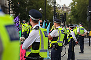Police officers not wearing face masks stand by at Parliament Square during an Extinction Rebellion climate change protest in London, Tuesday, Sept 1, 2020. (VXP Photo/ Vudi Xhymshiti)