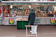 Nederland, Nijmegen, 6-4-2020Kaasboer op de markt. Personeel achter plastic scherm . Bescherming medewerkers, plastic  tussen klanten  en de kassa, verzoek 1,5 meter afstand  te houden in verband met corona besmetting .Foto: Flip Franssen