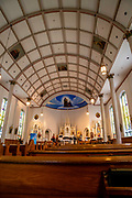 Interior view of St. Ann's Church with musicians practicing for a concert, Mackinac Island, Michigan, USA.
