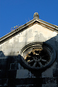 Detail of Saint Mark's (Sveti Marko) Cathedral showing rose window and Acroterium, Korcula old town, island of  Korcula, Croatia.
