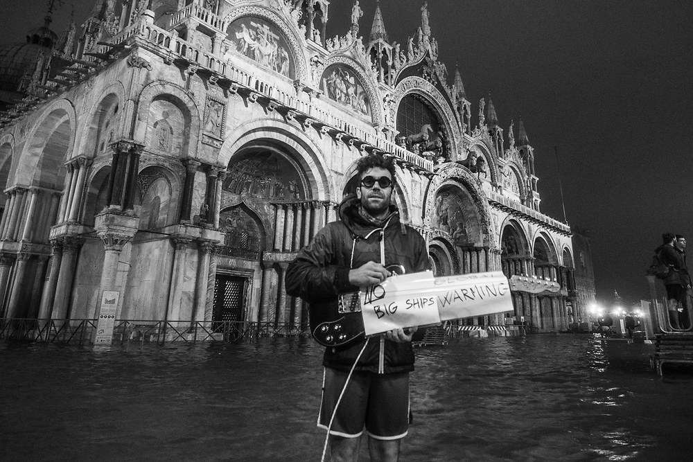 Venice, Italy. 29 October, 2018. A boy with a guitar and banners of protest for the passage of cruise ships and for the climate change, stand in St. Mark square on October 29, 2018, in Venice, Italy. This is a selection of pictures of different areas of Venice that the press has not covered, were resident live and every year they have to struggle with the high tide. Due to the exceptional level of the 'acqua alta' or 'High Tide' that reached 156 cm today, Venetian schools and hospitals were closed by the authorities, and citizens were advised against leaving their homes. This level of High Tide has been reached in 1979. © Simone Padovani / Awakening / Alamy Live News
