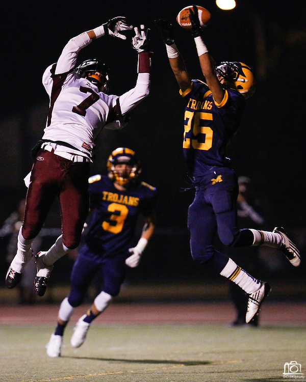 Milpitas' running back Curtis Hicks (25) and Piedmont Hills' wide receiver Aaron Tillak (7) battle for the ball in the air during the CCS Division 1 playoff game at Milpitas High School in Milpitas, California, on November 29, 2013. No. 2 Milpitas beat No. 3 Piedmont Hills 45-0. (Stan Olszewski/SOSKIphoto)