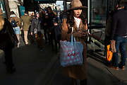 Stylish Chinese woman texting while waiting for her bus on Piccadilly during Chinese New Year celebrations in central London, United Kingdom. Tens of thousands of people gathered in the West End filling the streets and joining in with the festival atmosphere. (photo by Mike Kemp/In Pictures via Getty Images)