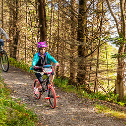 A man and his daughter ride bikes at Quoddy Head State Park in Lubec, Maine.