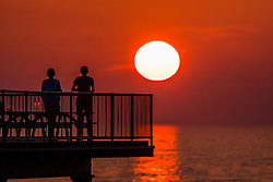 © Licensed to London News Pictures. 09/06/2018. Aberystwyth, UK. The setting sun in the orange sky silhouettes people enjoying a drink on  the Victorian seaside pier in Aberystwyth on the west coast of Wales, at the end of a day of hot summer sunshine. Photo credit: Keith Morris/LNP