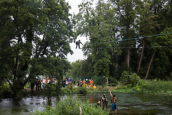 Denham, UK. 24 July, 2020. Larch, an environmental activist from HS2 Rebellion, moves across a line above the shallow river Colne attached to an ancient alder tree which he and other activists are trying to protect from destruction in connection with works for the HS2 high-speed rail link in Denham Country Park. A large policing operation involving the Metropolitan Police, Thames Valley Police, City of London Police and Hampshire Police as well as the National Eviction Team was put in place to enable HS2 to remove the tree.