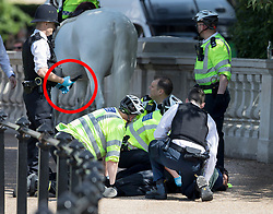 © Licensed to London News Pictures. 24/05/2017. London, UK. A policeman holds a knife as colleagues detain a man opposite Buckingham Palace just before the Changing of the Guard ceremony. Today's ceremony has been cancelled.  The terrorism threat level has been raised to critical and Operation Temperer has been deployed. 5,000 troops are taking over patrol duties under police command. Photo credit: Peter Macdiarmid/LNP