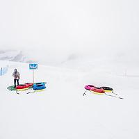 A tourist waits to enjoy some summer snow tubing, Jungfrau Joch, Switzerland.