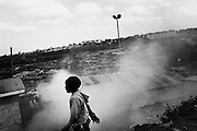 """NAIROBI, KENYA - AUGUST 27, 2011: Children walk along the railroad tracks amid waste and pollution in Kibera slum.<br /> <br /> Various grassroots initiatives led by youth have begun to improve the quality of life for those living in the direst of conditions, and young people of different tribes are using gardening, waste removal, education and athletics to encourage their peers toward a self-respecting and self-sustaining community. Termed """"youth groups"""" on the street, these initiatives could represent the future of long-term socioeconomic development in Kenya while laying the groundwork for a more peaceful election in 2013. During the post-election violence of 2007 and 2008, impoverished youth in Kenya were routinely bribed by the nation's political elite to carry out acts of violence in their communities. Idleness among the youth, combined with the nation's history of tribal rivalries, were cited as a key factors to the violence, culminating in the deaths of over 1,200 Kenyans and the displacement of over 600,000. Since the violence, many youth have begun to seize active roles in the reform of their nation. In 2010 United States Ambassador Michael Ranneberger said he sensed """"a sea change of attitude"""" among youths, """"a tidal wave below the surface. The youth have woken up."""""""
