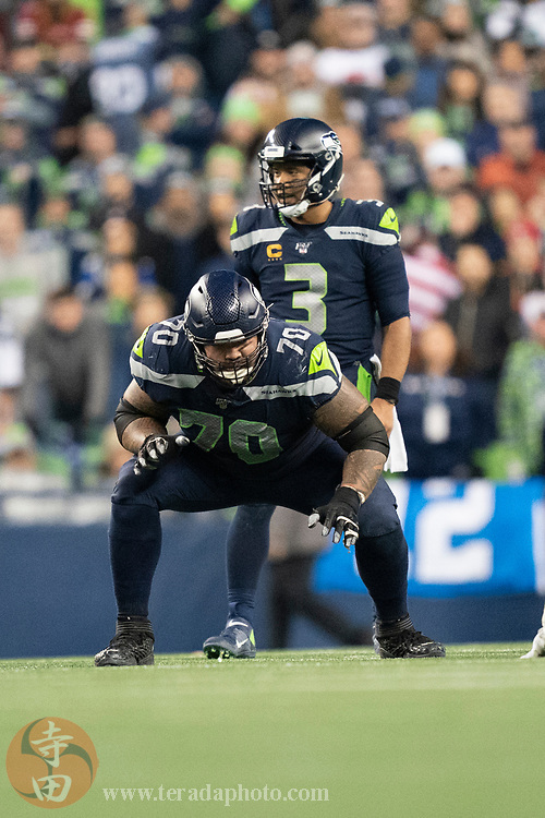 December 29, 2019; Seattle, Washington, USA; Seattle Seahawks offensive guard Mike Iupati (70) in front of quarterback Russell Wilson (3) during the fourth quarter against the San Francisco 49ers at CenturyLink Field.