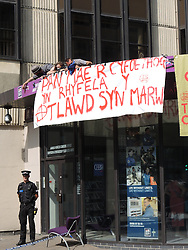 © Licensed to London News Pictures. 25/07/2014. Cardiff, UK. A group of 3 protesters scaled the roof of the armed Forces recruitment office in protest of current recruitment policy and UK involvement in NATO. The group, from Newport,where the NATO summit will be held in September, is part of the Anarchist Action Network. Beyond that they declined to give details. Police are monitoring the situation and have cordoned the area off for safety reasons. . Gavin O' Connor (Wales) Brigade Media Ops (07775823518) ironically claims they have handed out more leaflets to the public as a result of the action.  No arrests have been made so far. Protesters blog network23.org/stopnatocymru Photo credit : Ian Homer/LNP