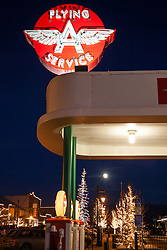 """""""The Flying A in Truckee 2"""" - Photograph of the Flying A in Downtown Truckee with a moon and Christmas lights in the background."""