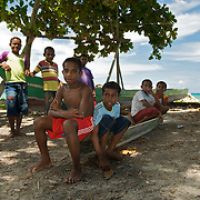 Papuan kids sitting on logboats in the shade.