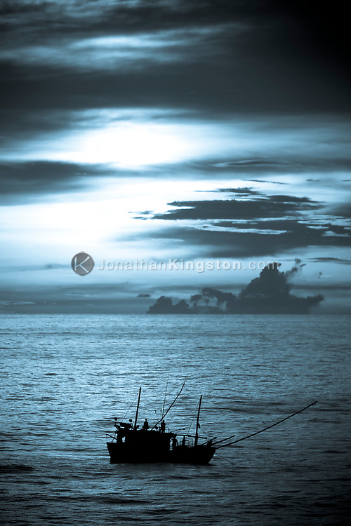 Silhouette of a fishing boat near Laem Chabang Port, Thailand.  Most of the international shipments reaching Thailand pass through the port of Laem Chabang.