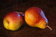 Two pears on a textured background with Rembrant lighting.