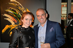 Winning Ryder Cup captain PAUL McGINLEY and his daughter NIAMH McGINLEY at a private view of paintings by Michael Flatley entitled Firedance held at 12 hay Hill, London on 24th June 2015.