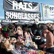 Tourist purchasing hats and sunglasses from market