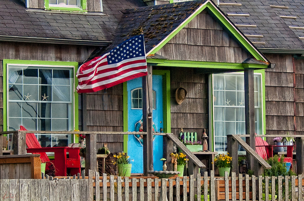 Quintessential beach cabin, gayly decorated will all the trappings of beach life and summer. The flag is flapping in the wind, the chairs are waiting, the plants are blooming. the fence more a decorative element than a barrier.
