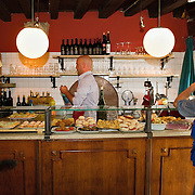 """VENICE, ITALY - JUNE 17:  Marco Petrocco serves cicchetti and wine to a local customer at """"La Vecia Carbonera"""" on June 17, 2011 in Venice, Italy. The bacari are the local down to earth version of wine bars, they serve  """"cicheti"""" a sort of Tapas, traditionally washed down with a glass of wine, and Venetians stop to snack and socialize before and after meals."""