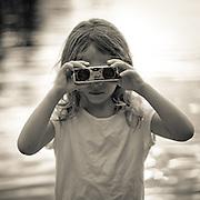 Girl looking through binoculars on Lake Kezar