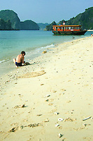 Boy playing in the sand on Monkey Island Beach at Lan Ha Bay.  The beach and bay are popular day trip spots on Halong Bay for some water sports, or just relaxing on the beach.