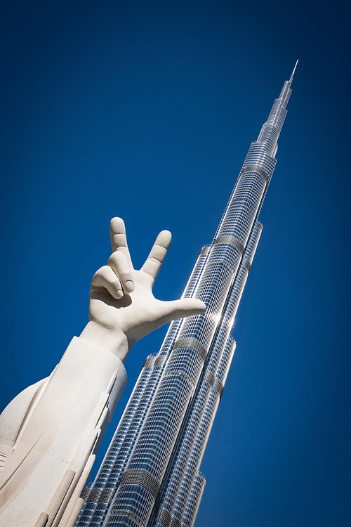 Win Victory Love hand sculpture on the banks of the Burj Khalifa Lake with the Burj Khalifa Building. It symbolizes work ethic, success, and love of the nation and has become a trademark of the UAE. Coined by His Highness Sheikh Mohammed bin Rashid Al Maktoum