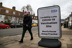 © Licensed to London News Pictures. 16/03/2021. London, UK. A woman wearing a face covering walks past a vaccination centre sign in north London. The European Medical Agency (EMA) has said that there is no indication that the Oxford-AstraZeneca Covid-19 vaccine causes blood clots, after several countries paused their rollouts. Photo credit: Dinendra Haria/LNP
