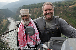 Kelly Modlin with a local on the Kusma Gyadi Bridge, the tallest (443') and one of the longest (1,128') suspension bridges in the country, on Day-7 of our Himalayan Heroes adventure riding from Tatopani to Pokhara, Nepal. Monday, November 12, 2018. Photography ©2018 Michael Lichter.