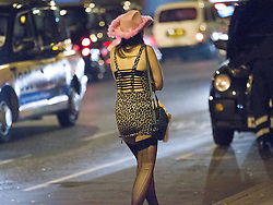 """© Licensed to London News Pictures . 22/10/2012 . Manchester , UK . A female student in a pink cowboy hat and heavily laddered tights amongst taxi cabs . Students attend a Carnage UK pub crawl at bars in Manchester 's Deansgate Locks with a fancy dress theme of """" Pimps and Hoes """" . The event has been criticised for encouraging binge drinking , sexism and anti-social behaviour . Photo credit : Joel Goodman/LNP"""