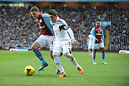 Aston Villa's Matthew Lowton and Swansea City's Pablo Hernandez battle for the ball during the Barclays Premier league, Aston Villa v Swansea city at Villa Park in Birmingham, England on Saturday 28th Dec 2013. <br /> pic by Jeff Thomas, Andrew Orchard sports photography.