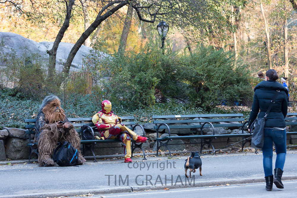Movie characters in costume chilling out on park bench as woman passes walking a dog in Central Park, New York, USA