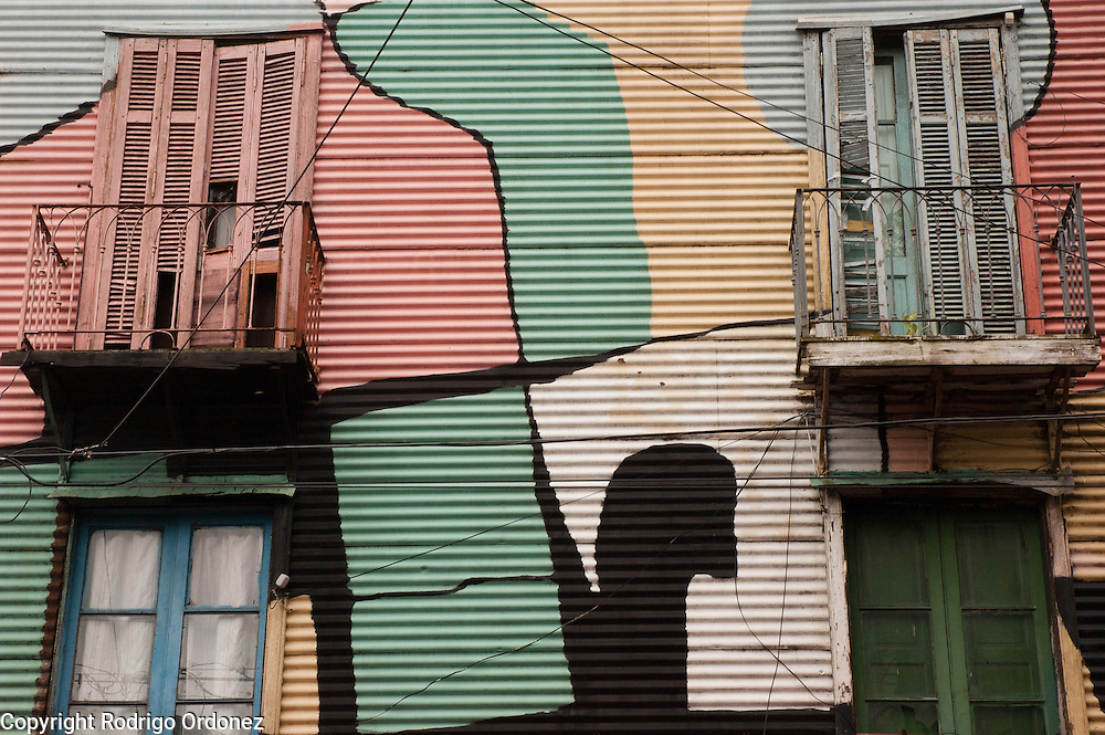 View of balconies and windows decorated with paint in Caminito street, in La Boca neighborhood of Buenos Aires, Argentina.<br /> Caminito is a pedestrian street created in the late 1950s by local painter Benito Quinquela Martín and other artist friends to recreate a version of the old immigrant neighborhood of La Boca, using wood and corrugated zinc painted in bright colors. Today, Caminito and the surrounding areas feature cafes, souvenir shops, tango dancers and other street performances aimed to attract tourists.