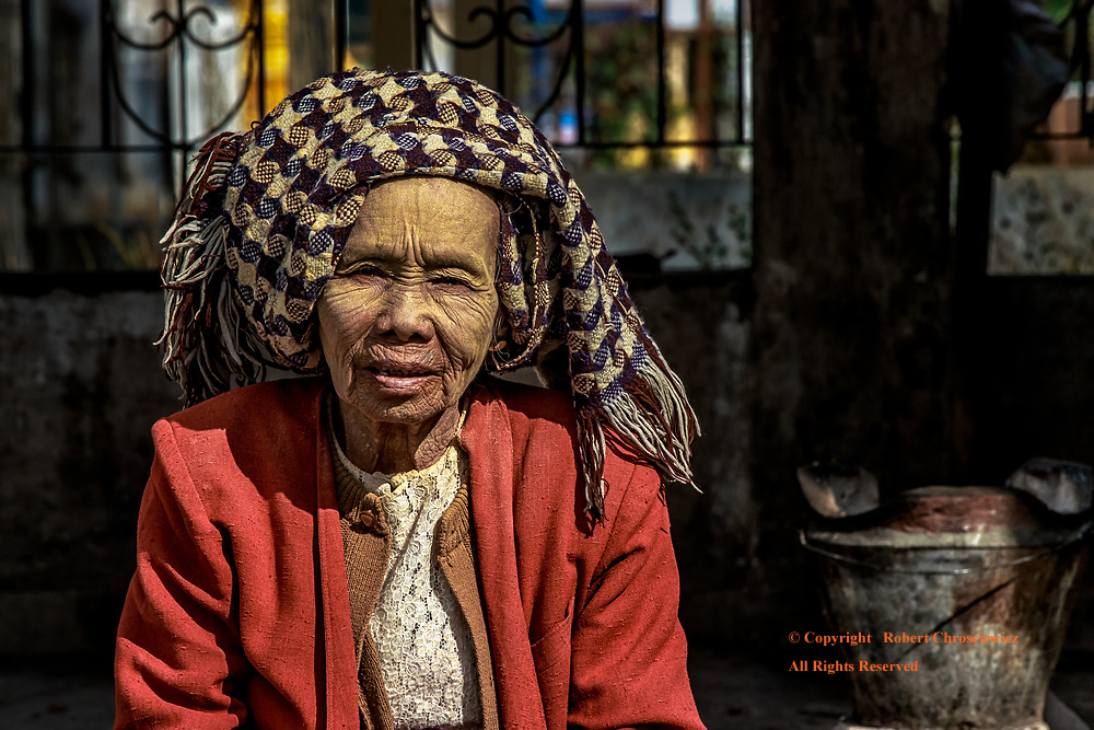 Morning Madame: An older woman wears both thanaka on her face and her head dress as she pauses from her kitchen chores, Inle Lake Myanmar.