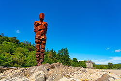 Gormley Land sculpture looks out over the Kilbrannan Sound to Arran from the rocks below Saddell Castle in Kintyre peninsula, Argyll and Bute, Scotland, Uk