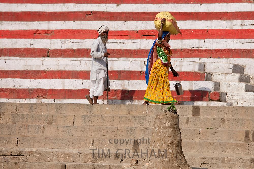 Indian man and woman walking along Rana Mahal Ghat by the Ganges River in City of Varanasi, Benares, Northern India