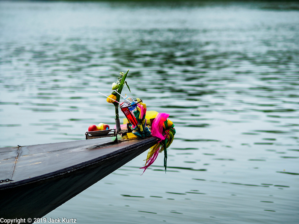 """09 JANUARY 2019 - KANCHANABURI, THAILAND:  An offering on the bow of a small ferry that takes people acrss the River Kwai. The ferry goes across the River Kwai downriver from downtown Kanchanaburi, the site of the famous """"Bridge on the River Kwai."""" Small ferries like this, once common on Thai river crossings, are disappearing because Thailand has dramatically improved its infrastructure since this ferry started operating about 50 years ago. The ferry operator said his grandfather started the ferry, with a small raft he would pole across the river, in the late 1960s. Now his family has a metal boat with an inboard engine. There are large vehicle bridges across the river about 5 miles north and south of this ferry crossing, but for people in rural communities on the west side of the river the ferry is still the most convenient way to cross the river.     PHOTO BY JACK KURTZ"""