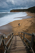 A surfer runs onto Bells Beach to catch the large winter swells. Located near Torquay, Victoria, Australia, Bells Beach is famous for its surfing. The area is part of the Great Ocean Road.
