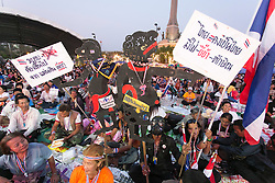 © Licensed to London News Pictures. 16/01/2014. Colourful Anti-Government protestors hold up banners with Anti-Government statements during the fourth day of the 'Bangkok Shutdown' as anti-government protesters continue with their 'shutdown' of Bangkok.  Major intersections in the heart of the city have been blocked in their campaign to oust Prime Minister Yingluck Shinawatra and her government in Bangkok, Thailand. Photo credit : Asanka Brendon Ratnayake/LNP