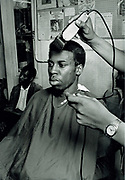 Youth gets a hair cut in local barber shop. Photo by Richard Saunders 1983