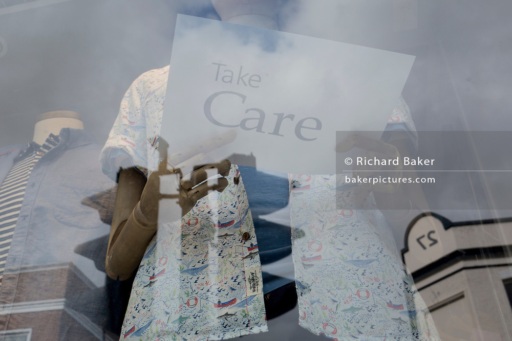 At the beginning of the second week of the UK's Coronavirus lockdown and in accordance with government guidelines for social distancing and the forced closure of all shops and local businesses, the wooden fingers of a mannequin holds a sign saying Take Care, in the window of a clothing shop in East Dulwich, on 30th March 2020, in London.