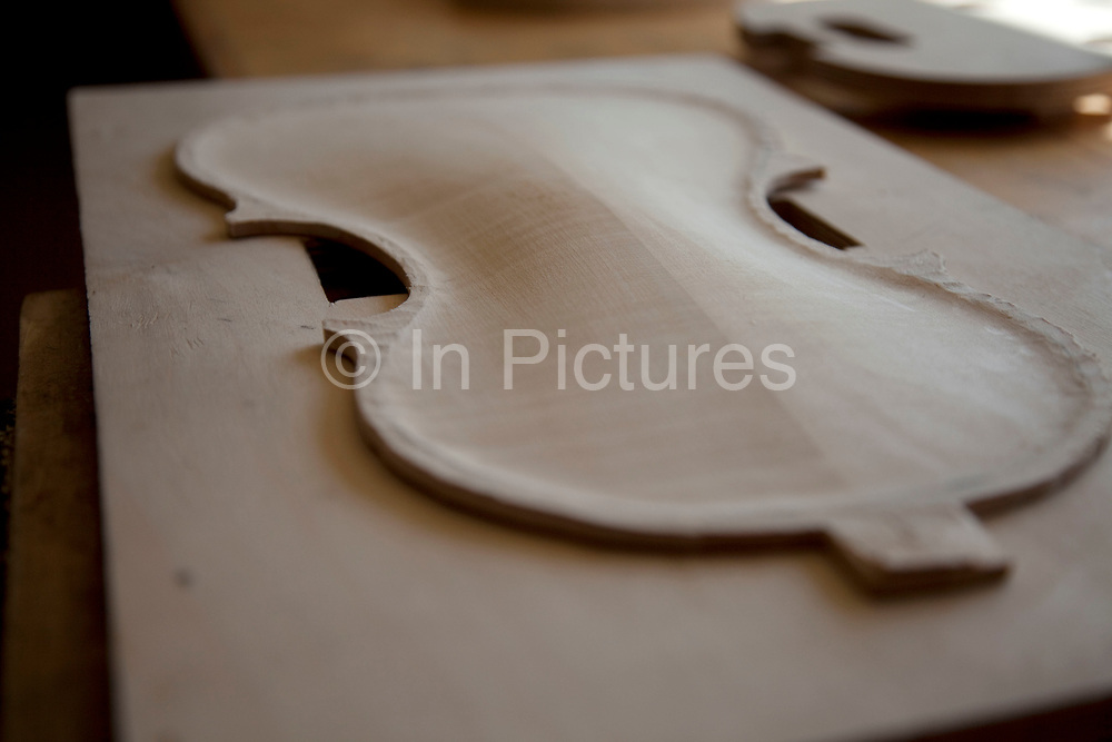 Front being finely planed down. Violins being made at viloin an cello maker, Rod Ward's studio in Guilden Morden, Hertfordshire, UK. This highly skilled craft involves the process of making from raw wood to final instrument. All hand crafted with specialist tools and care for detail.