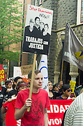 Demonstrator in 2015 May Day rally and march in Portland, Oregon holds a sign saying Trabajos con Justicia - Stop Deportations