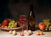 Classic still life featuring a colorful bowl of fruit and a wine bottle with a wineglasses on a black background