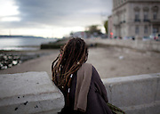 A girl watching the river Tagus from Cais das Colunas, the place where old caravels used to leave to India. This photograph is part of a body of work about Lisbon, feelings, affections and loneliness. Is about a city depressed by the crisis, but even so, tolerant and cosmopolitan. This part of Lisbon, the old town near the river Tejo (Tagus), with his deep character, where local people meets foreigners and alternative ways of life mixes with shamefaced poverty, is sublime by its peculiar light.